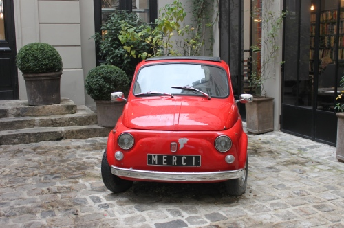 Red fiat at the entrance to Merci Paris